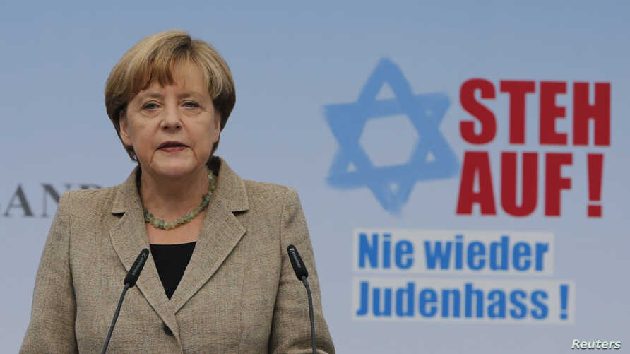 "German Chancellor Angela Merkel, standing in front of a sign that reads ""Stand up!"" makes an address during an anti-Semitism demonstration at Berlin's Brandenburg Gate, Sept. 14, 2014."