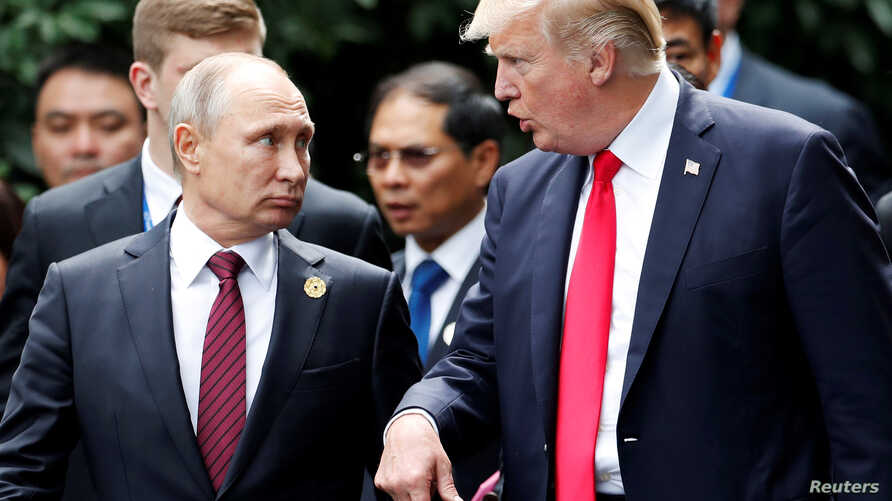 U.S. President Donald Trump and Russia's President Vladimir Putin talk during the photo session at the APEC Summit in Danang, Vietnam, Nov. 11, 2017.