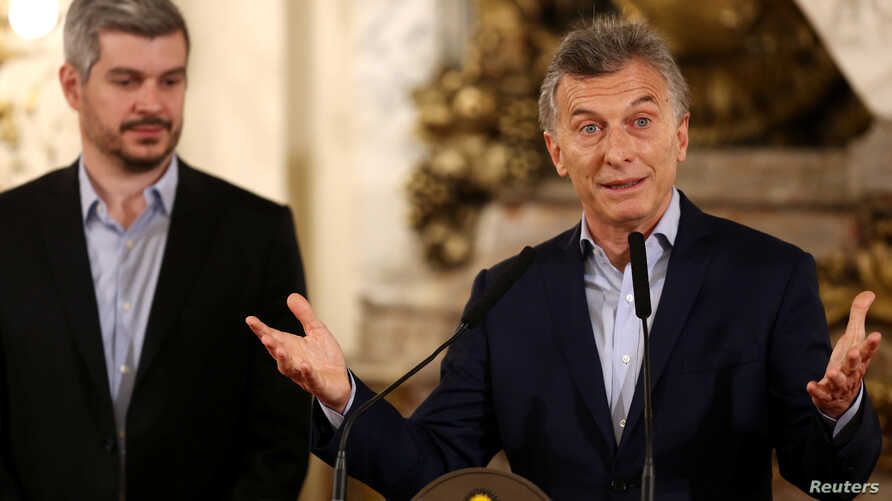 Argentina's President Mauricio Macri speaks next to Cabinet Chief Marcos Pena during a news conference at the Casa Rosada Presidential Palace in Buenos Aires, Argentina, Oct. 23, 2017.