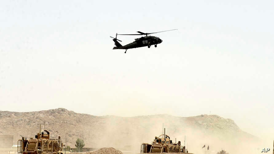 A U.S. military helicopter flies over the site of a suicide bomb attack on a NATO convoy in Kandahar, south of Kabul, Afghanistan, Aug. 2, 2017.