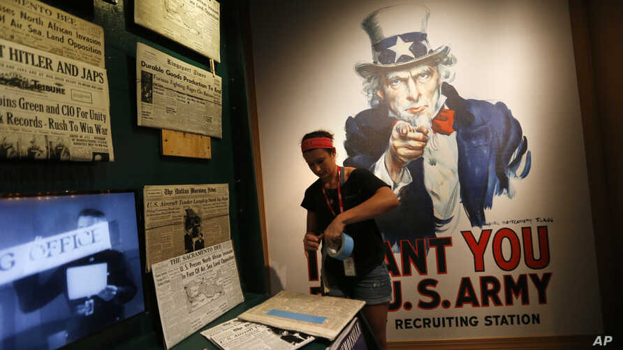 """Kristin Guillot works on installing images of newspapers as part of the permanent exhibit """"Salute to the Home Front"""" at the National World War II Museum which will open to the public in New Orleans, June 5, 2017."""