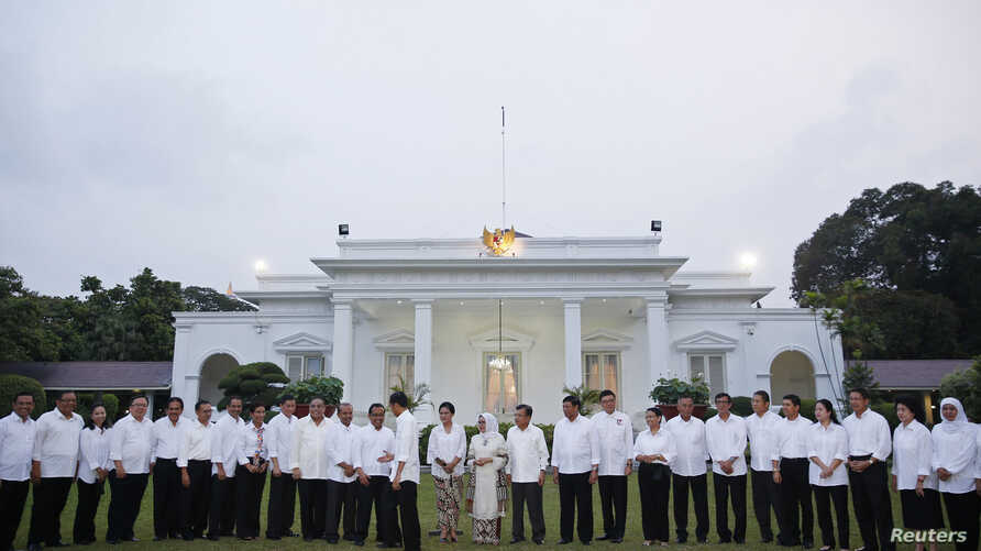 Indonesian President Joko Widodo shakes hands with members of his new cabinet after they were unveiled at the presidential palace in Jakarta, Oct. 26, 2014.