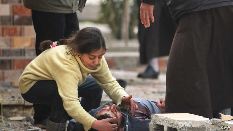 An Iraqi girl cries over her father's body, who was killed by a mortar shell fired by Islamic State (IS) group jihadists on civilians who were gathered to receive aid, in Al-Risala neighbourhood on March 22, 2017, as an ongoing offensive by Iraqi for