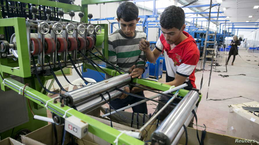 Palestinians work at a textile factory in the Industrial Park of the West Bank Jewish settlement of Barkan, Nov. 8, 2015. Few issues have caused more friction between Israel and the European Union than EU plans to impose labeling on goods produced in