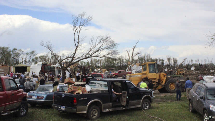 Dozens of people gather to help with cleanup efforts at a farm that was severely damaged by a tornado Sunday, May 10, 2015, in Delmont, South Dakota.