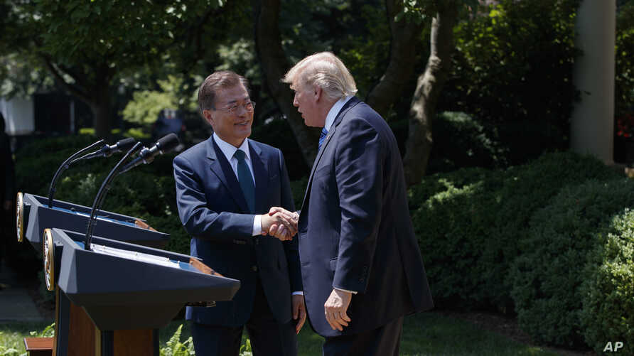 South Korean President Moon Jae-in shakes hands with President Donald Trump, right, after making statements in the Rose Garden of the White House in Washington, June 30, 2017.