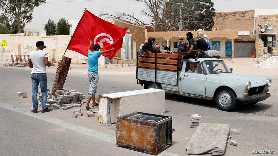 Protesters, who are demanding jobs and a share in revenue from the area's natural resources, block the road usually used by foreign oil companies to go the oil field in Tataouine, Tunisia, May 12, 2017. Picture taken May 12, 2017.
