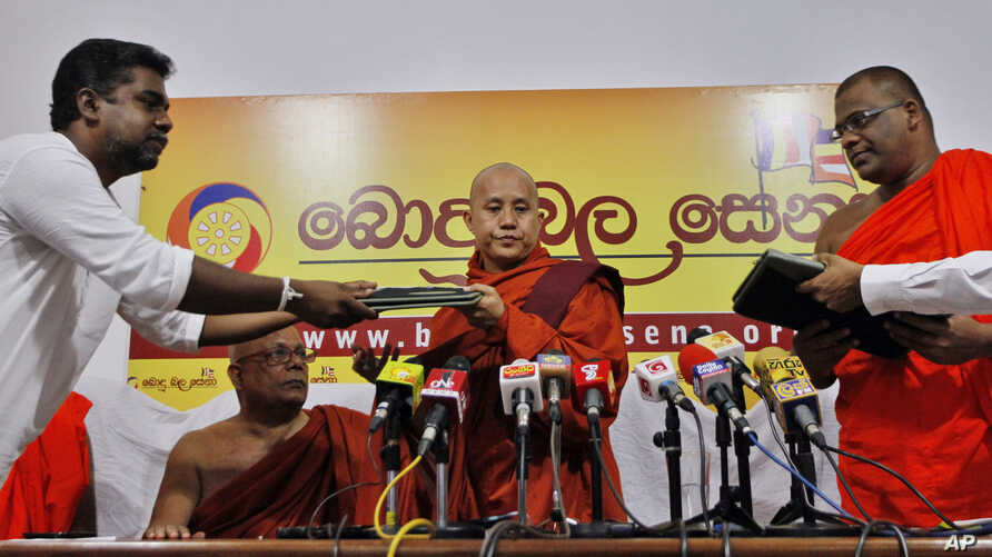 Myanmar's radical Buddhist monk Ashin Wirathu, center, exchanges copies of a three-point agreement with the officials of Sri Lanka's Bodu Bala Sena or Buddhist Power Force during a media briefing in Colombo, Sri Lanka, Sept. 30, 2014.