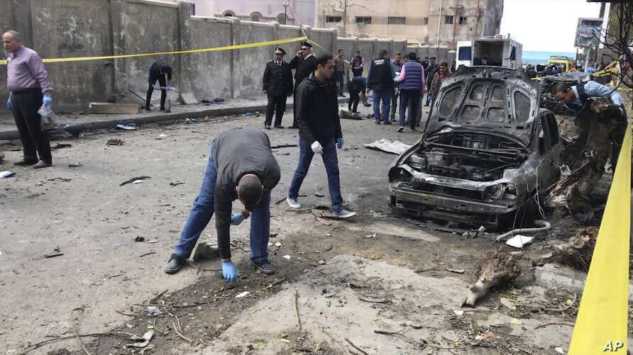 Investigators search the area after a bomb placed under a car exploded, in Alexandria, Egypt, March 24, 2018.
