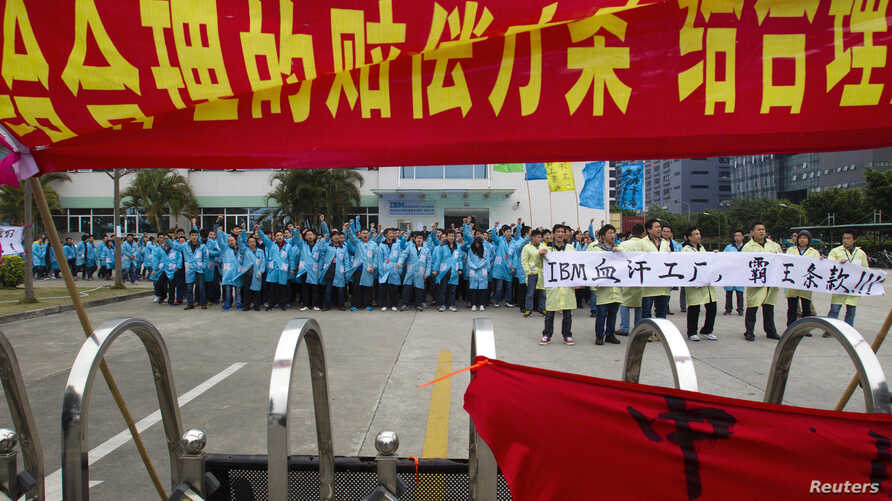 IBM workers shout slogans and hold banners as they protest at an IBM factory in Shenzhen, Guangdong province, March 7, 2014.