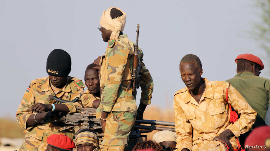 Armed members of the South Sudanese security forces are seen during a ceremony marking the restarting of crude oil pumping at the Unity oil fields, Jan. 21, 2019. Beginning in March, the government will deduct one day's salary from civil servants' pa