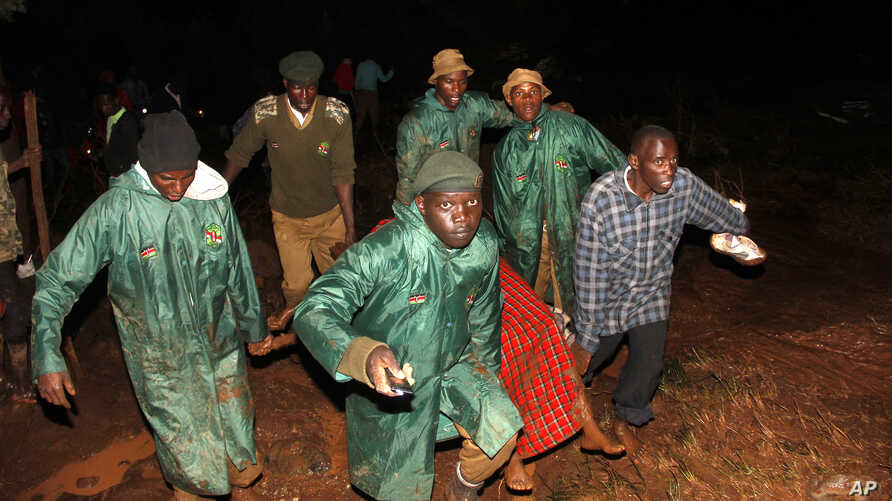Members of the National Youth Service carry away a dead body covered in a blanket during the early hours of  May 10, 2018 near Solai, in Kenya's Rift Valley.