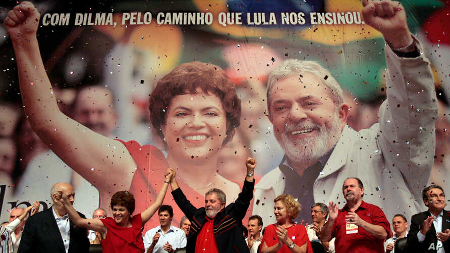 FILE - Brazil's President Luiz Inacio Lula da Silva, center, raises arms with his Chief of Staff Dilma Rousseff at an annual Workers Party Congress in Brasilia, Brazil, where the party announced Rousseff as the party's 2010 presidential candidate, Fe