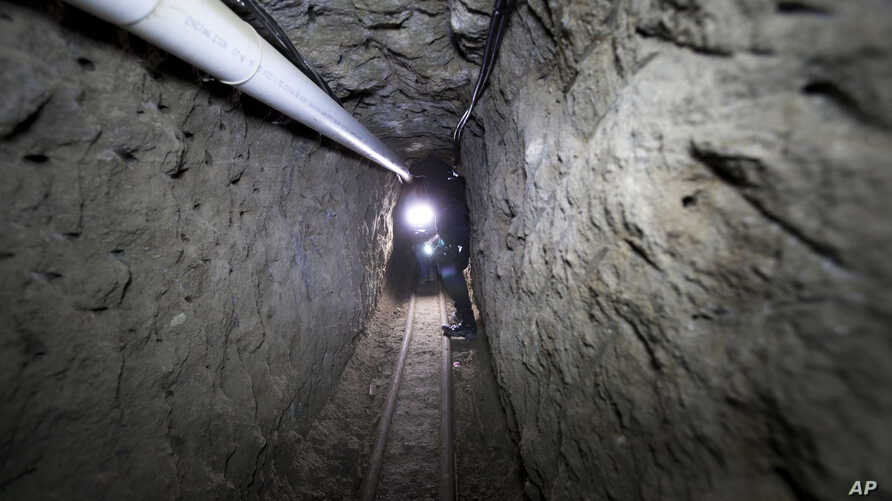 """Federal Police officer stands in the tunnel where according to authorities drug lord Joaquin """"El Chapo"""" Guzman made his escape from the Altiplano maximum security prison in Almoloya, west of Mexico City, July 16, 2015."""