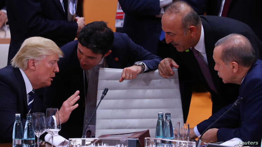 U.S. President Donald Trump, left, Turkish President Recep Tayyip Erdogan and Turkey's Foreign Minister Mevlut Cavusoglu, standing right, talk during the working session at the G20 leaders summit in Hamburg, Germany, July 7, 2017.