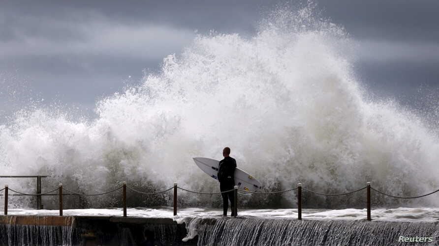 A cyclonic storm lashed Australia's east coast for a third day Wednesday, causing millions of dollars of damage to property and infrastructure. A surfer waits for a break in crashing waves before diving in for a surf off Sydney's Collaroy Beach, Apri