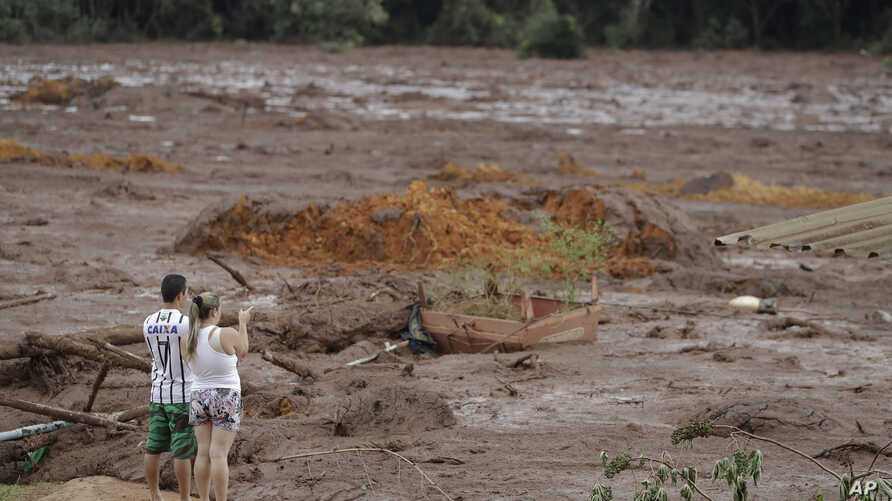 A couple with missing relatives look at the flooded area, after a dam collapsed in Brumadinho, Brazil, Jan. 26, 2019. An estimated 300 people were still missing and authorities expected the death toll to rise during a search made more challenging by ...