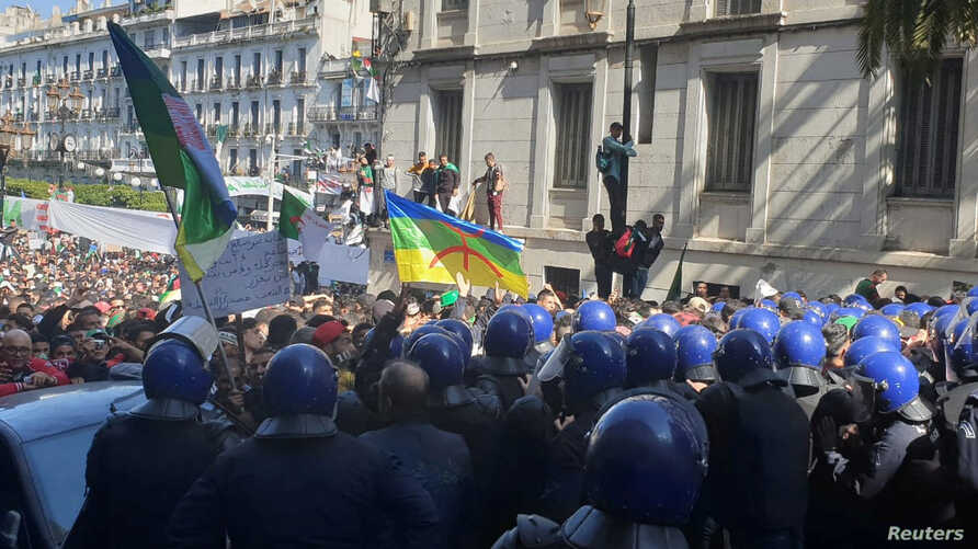 Police officers try to prevent protesters from advancing towards the government building during a protest to demand the removal of President Abdelaziz Bouteflika in Algiers, Algeria, March 29, 2019.