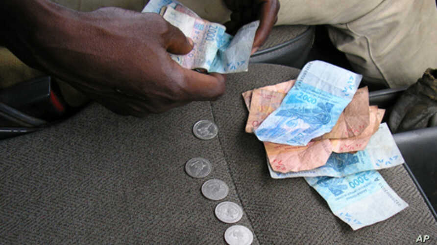 Some economists say ending the peg between CFA francs, shown here on a bus in Abidjan, and the euro would help West and Central African economies.