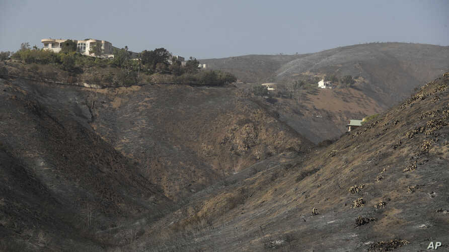 A home stands alone, at left, among the devastation left behind by a wildfire, Nov. 12, 2018, in Malibu, California.
