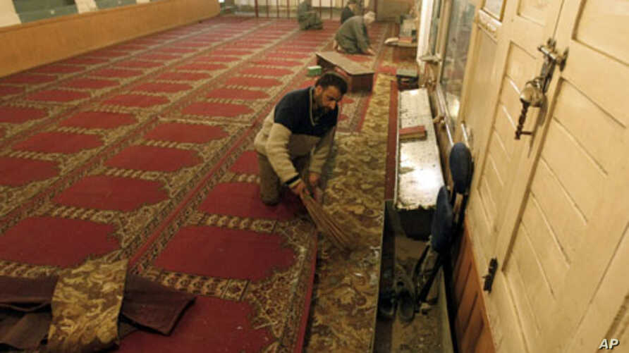 A Kashmiri man clears broken glass and debris inside a mosque after an explosion outside the mosque in Srinagar April 8, 2011.