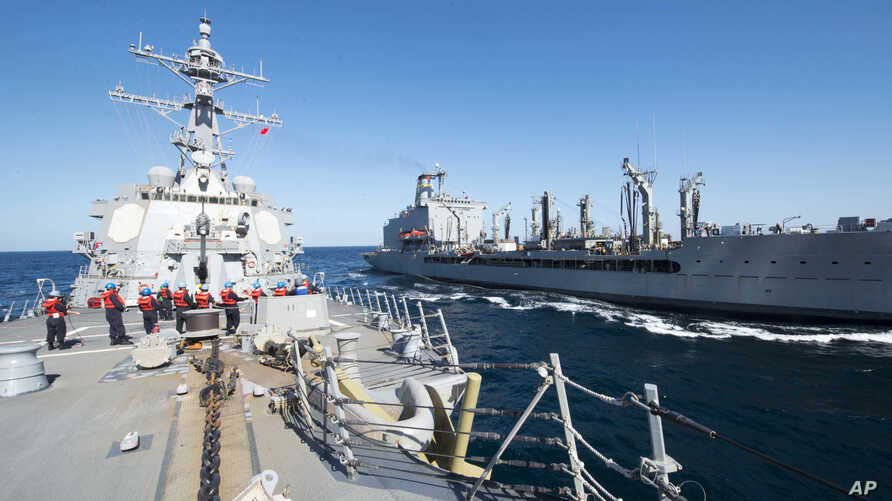 FILE - Guided-missile destroyer USS Bulkeley participates in a replenishment-at-sea with fleet replenishment oiler USNS John Lenthall in the Gulf of Oman. Iranian naval vessels conducted rocket tests last week near the USS Harry S. Truman aircraft ca