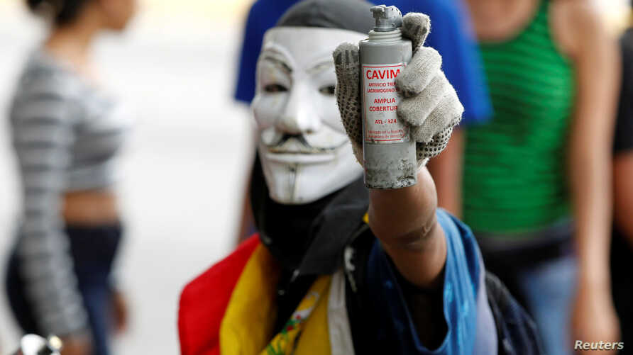 "An opposition demonstrator shows a tear gas grenade while clashing with riot police during the so called ""mother of all marches"" against Venezuela's President Nicolas Maduro in Caracas, Venezuela, April 19, 2017."