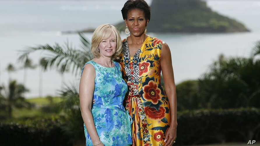FILE - U.S. First Lady Michelle Obama poses with Laureen Harper, spouse of Canadian Prime Minister Stephen Harper at Kualoa Ranch on the east side of Oahu in Kaaawa, Hawaii November 13,2011. The island of Mokolii, also know as the Chinaman's Hat isla