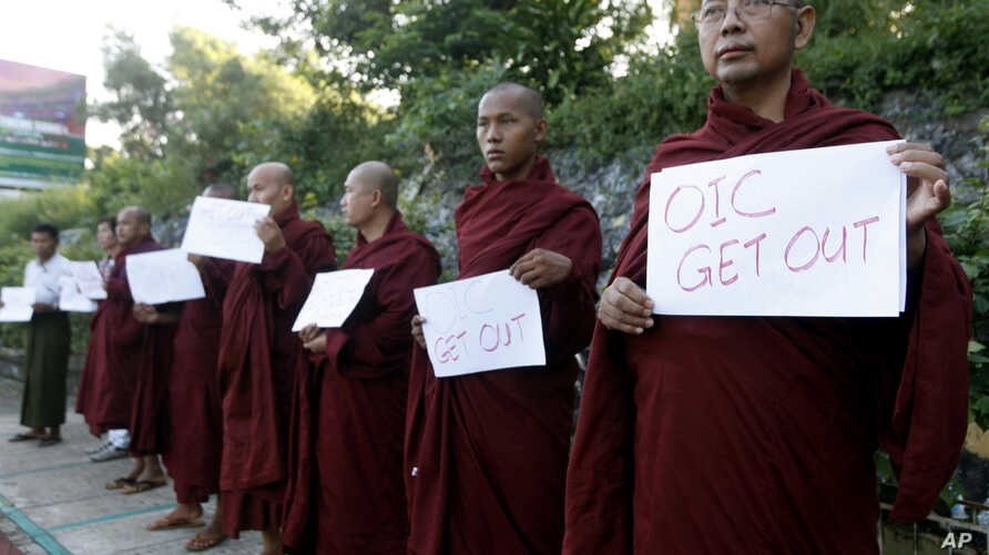 """Buddhist monks hold banners reading """"OIC Get Out"""" as they protest against the arrival of a delegation from the Organization of Islamic Cooperation, at Yangon International Airport, Nov. 13, 2013, in Rangoon, Burma."""
