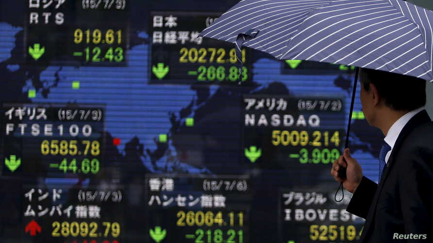 A pedestrian holding an umbrella looks at an electronic board the stock market indices of various countries outside a brokerage in Tokyo, Japan, July 6, 2015.