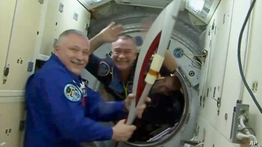 In this image made from video provided by NASA, cosmonaut Fyodor Yurchikhin, International Space Station commander, holds the Sochi 2014 Winter Olympics torch, Nov. 7, 2013.