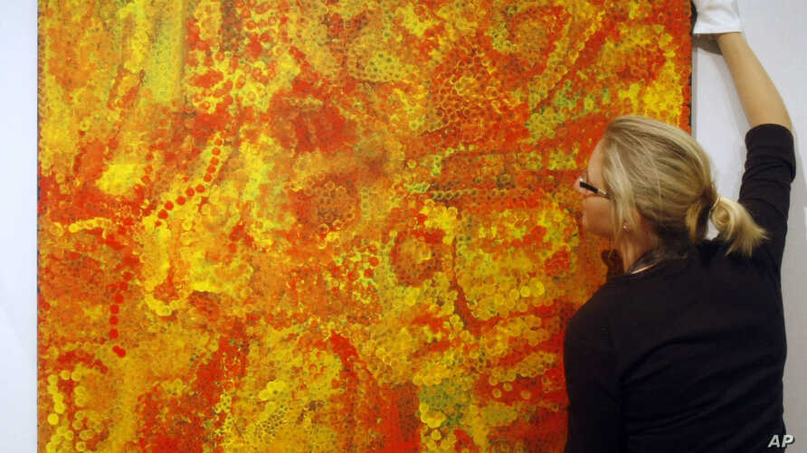 FILE - Christie's employee Rhiannon Broomfield poses for photographs beside the untitled painting by Aboriginal artist Emily Kame Kngwarreye which features in the forthcoming Modern and Contemporary Australian Art auction at the auction house's offic