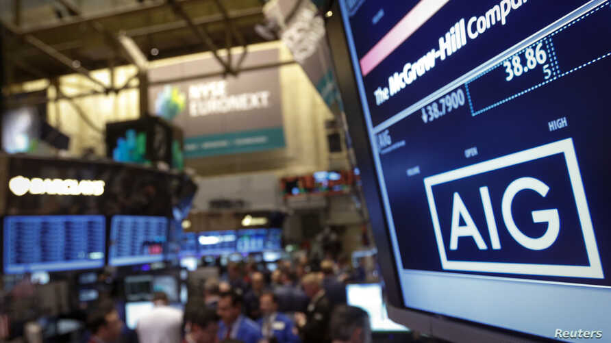 FILE - The American International Group Inc. (AIG) stock ticker is seen on a monitor as traders work on the floor of the New York Stock Exchange after the opening bell Feb. 11, 2013.