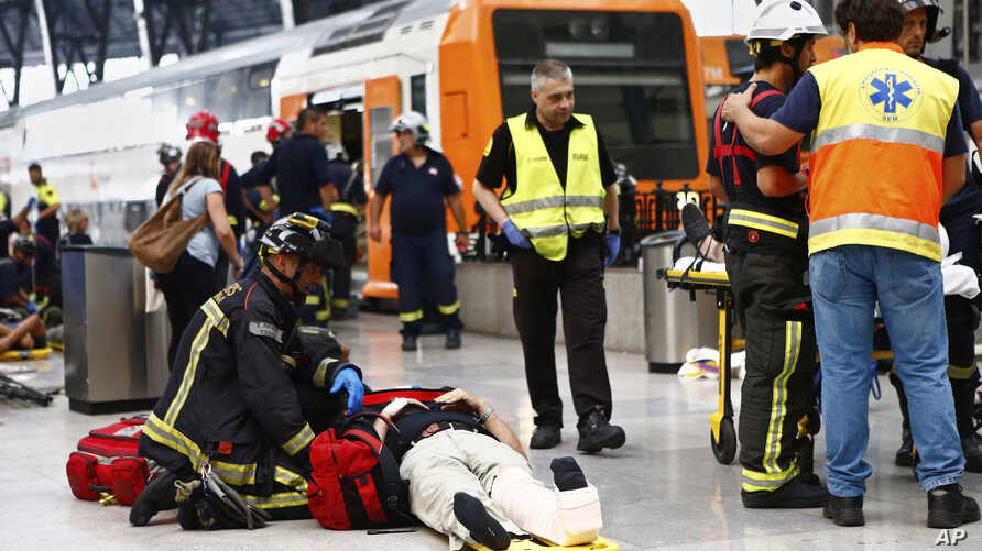 An injured passenger is attended to on the platform of a train station in Barcelona, Spain, July 28, 2017.