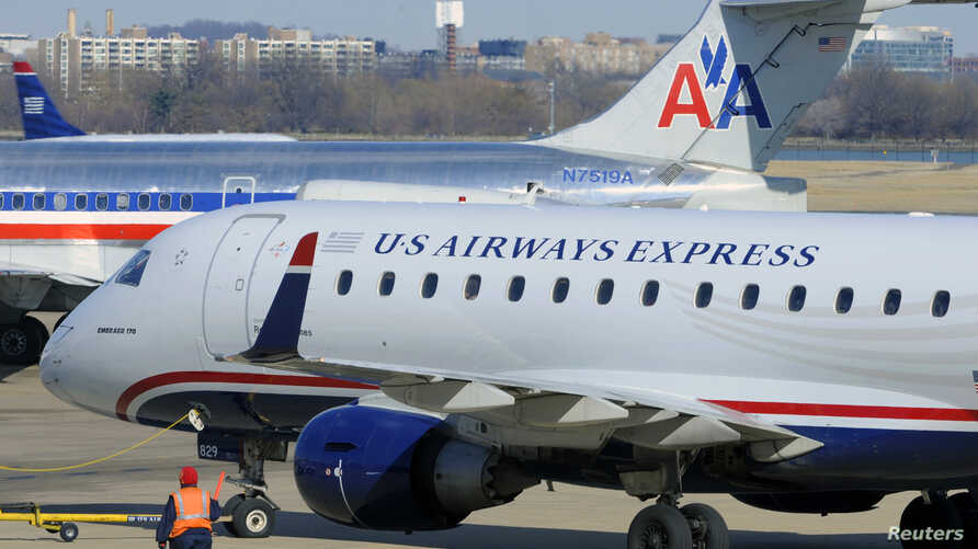 A US Airways Express plane departs from a gate past an American Airlines plane at the Ronald Reagan Washington National Airport in Arlington County, Virginia, February 10, 2013.