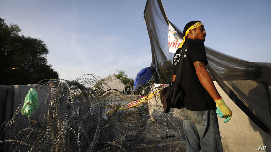 An anti-government protester stands in front of barbed wire set up by police near the compound of Thai Prime Minister Yingluck Shinawatra's office in Bangkok, Dec. 2, 2013.