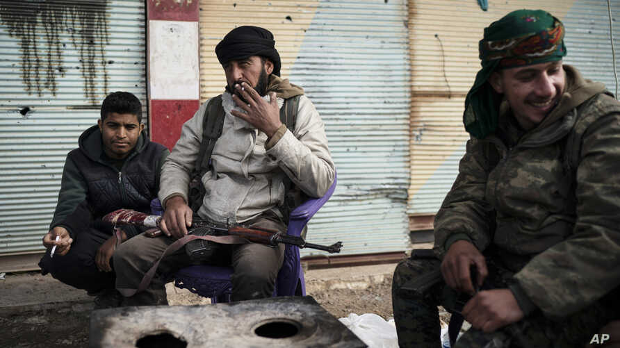 U.S.-backed Syrian Democratic Forces (SDF) fighters sit outside a building as fight against Islamic State militants continue in the village of Baghouz, Syria, Feb. 16, 2019.