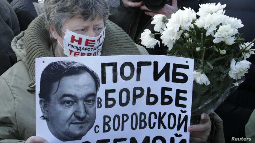 """FILE - A woman holds a placard with a portrait of Sergei Magnitsky during an unauthorized rally in central Moscow December 15, 2012. The placard reads """"Died fighting a system of thievery."""""""