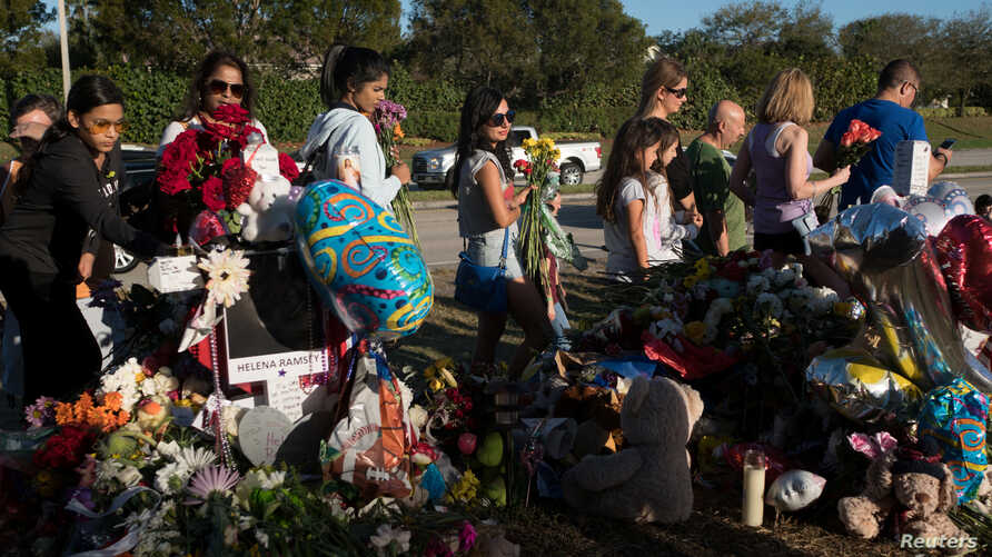 Well-wishers place flowers the day students and parents arrive for voluntary campus orientation at the Marjory Stoneman Douglas High School, Feb. 25, 2018. The school reopens Wednesday, following the Valentine's Day mass shooting in Parkland, Florida