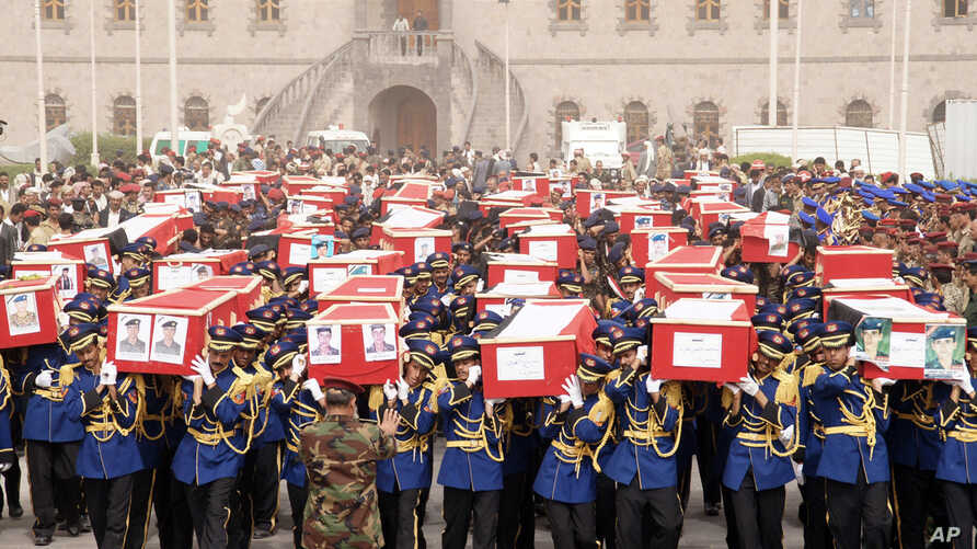In this handout photo provided by the Defense Ministry, Yemeni officers and soldiers carry coffins of soldiers who were killed in a suicide bomb attack at a parade square during their funeral procession in Sanaa, Yemen, Thursday, May 24, 2012. A Yeme