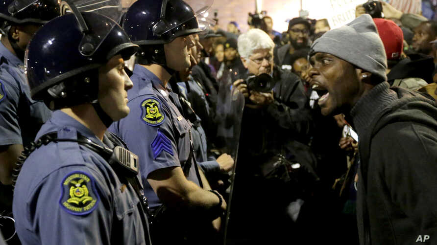 A protester yells at a Missouri State Police officer during a protest at the Ferguson, Missouri, police headquarters, Oct. 10, 2014.