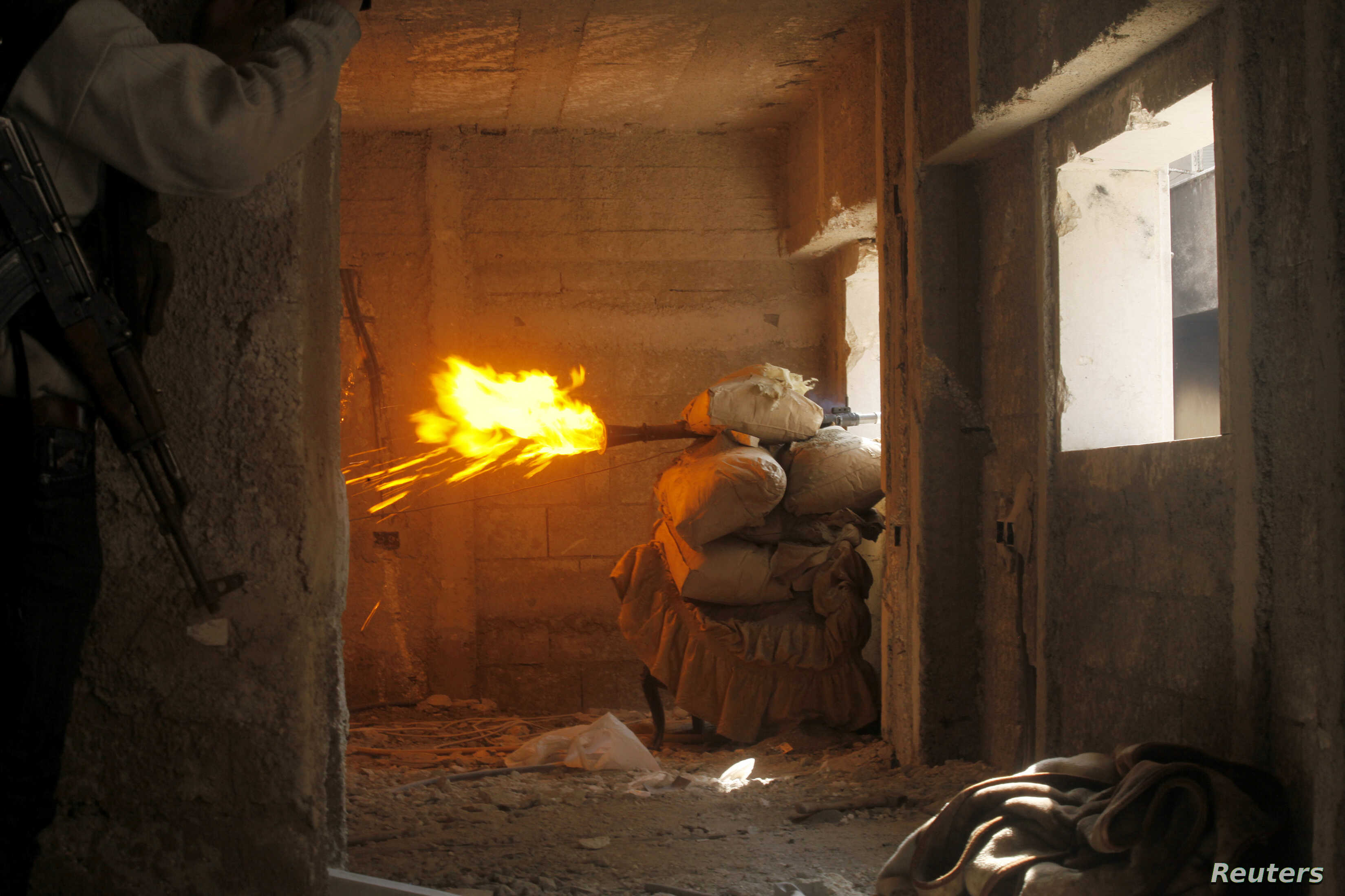 Free Syrian Army fighters take cover while firing a rocket on the front line in Izaa district in Aleppo Feb. 24, 2013.