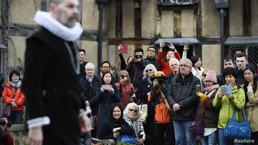 Tourists watch actors perform at the house where William Shakespeare was born during celebrations to mark the 400th anniversary of the playwright's death in Stratford-Upon-Avon, Britain, April 23, 2016.