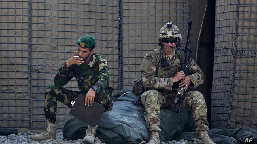 FILE - In this Aug. 5, 2015 photo, an Afghan National Army soldier, left, smokes as a U.S. Army soldier from Charlie Company, 2-14 Infantry Regiment, 2nd Brigade, 10th Mountain Division sits next to him in Camp Khogyani in Nangarhar province, east of