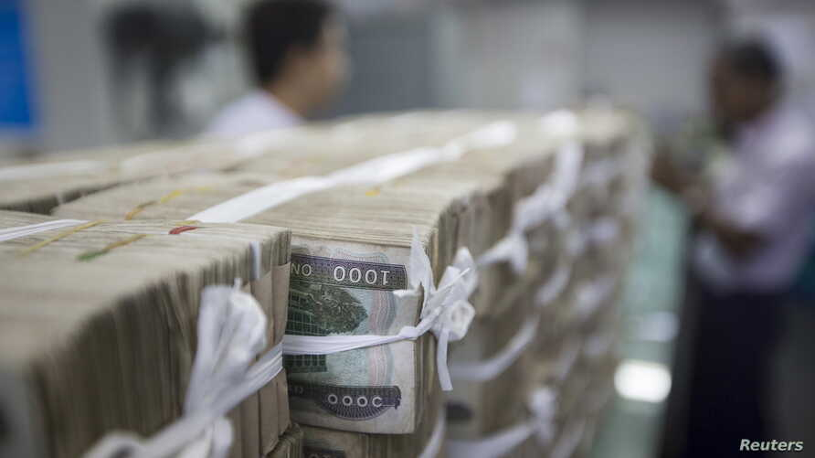 FILE - Stacks of Myanmar kyat are seen on the counter before a client collects them, at a bank in Yangon, Myanmar October 19, 2015.
