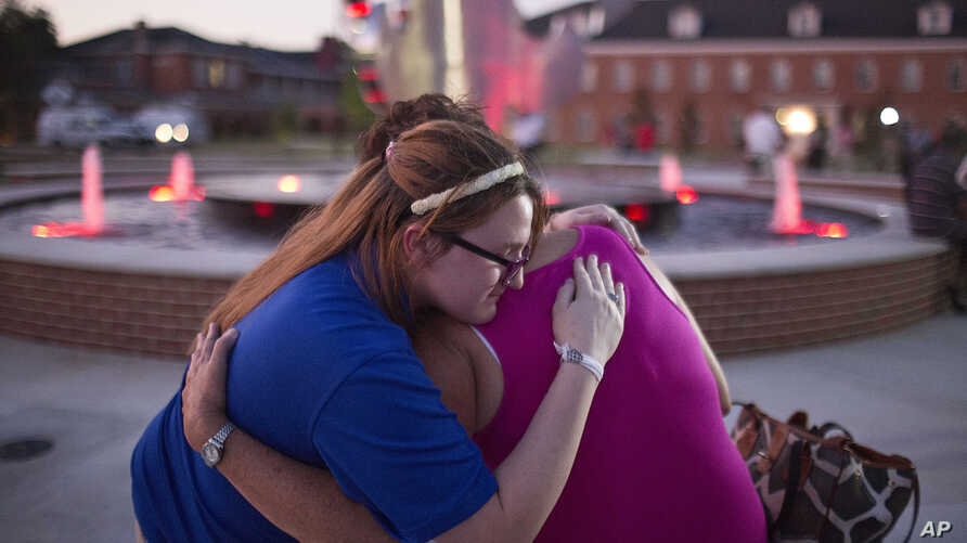 Christina Walls, left, and Diana Lennon embrace during a candlelight vigil July 24, 2015, to honor victims killed a day earlier in a movie theater in Lafayette, La.