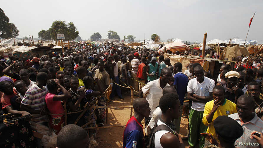 People displaced by the recent unrest, wait to collect food distributed by aid agencies at an IDP camp at the Mpoko International Airport of Bangui, Central African Republic, Feb. 12, 2014.