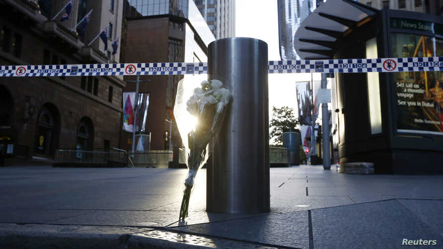 A bouquet is pictured under police tape near the cordoned-off scene of a hostage taking at Martin Place after it ended early Dec. 16, 2014.
