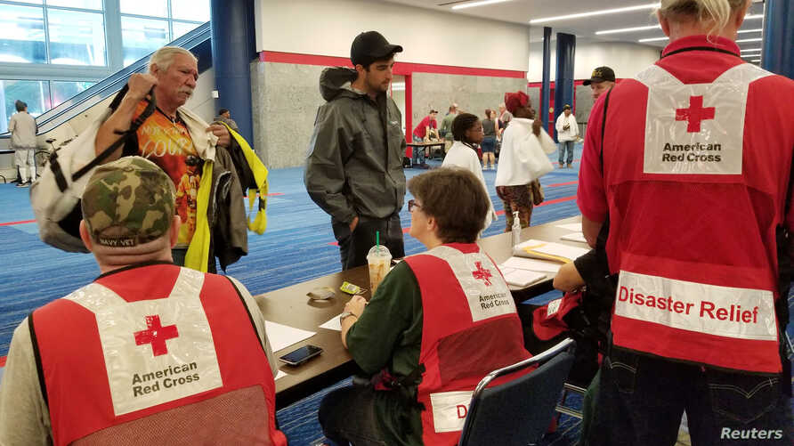 Evacuees arrive to seek shelter with Red Cross volunteers at the George Brown convention center after flood waters of Hurricane Harvey forced them to leave their homes in Houston, Aug. 27, 2017.