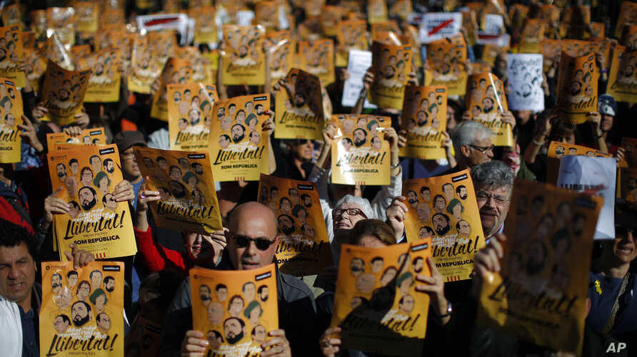 """Demonstrators holding banners that read in Catalan: """"Freedom for the Political Prisoners,"""" are seen during a protest against the decision of a judge to jail ex-members of the Catalan government, at University square in Barcelona, Spain, Nov. 5, 2017."""